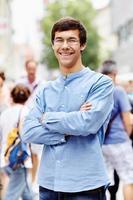 ung man med korsade armar utomhus foto