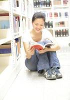högskolestudent i biblioteket foto