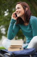 glad casual student sitter på bänken ringer foto
