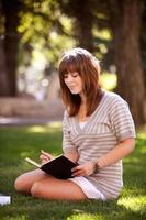 student med journal i park foto