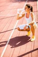 sportig ung kvinna dricksvatten foto