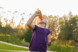 flickan dricker juice från flaskan foto