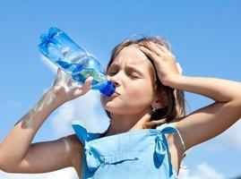 ung vacker flicka dricksvatten foto