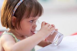 liten flicka som dricker vatten utomhus foto