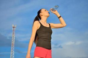 kvinna dricker vatten från flaskan foto