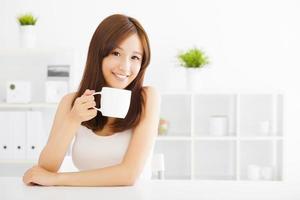 glad asiatisk ung som dricker kaffe foto