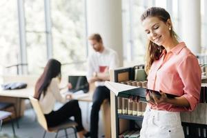 vacker kvinna som läser en bok i ett bibliotek