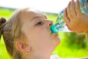 söt flicka dricksvatten foto