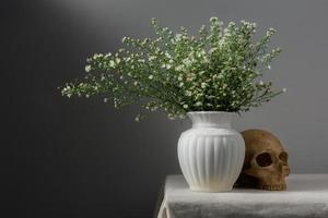 stilleben med blommor i vas och skalle foto