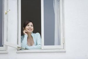 kvinna som ler vid fönstret foto