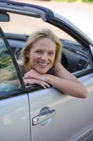 kvinna sitter i körplats på parkerad bil på uppfart