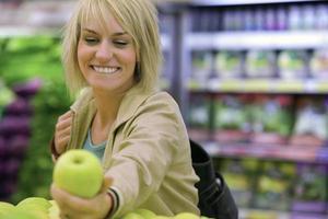 kvinna som väljer grönt äpple från skärm i snabbköpet (differen foto