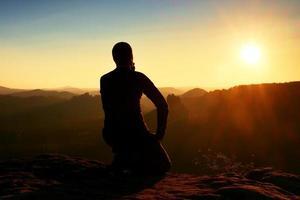 sportsmann vandrare sitter och tittar ner till morgonen dimmiga dalen. foto