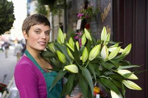 kvinnlig blomsterhandlare med massa blommor, leende, porträtt foto
