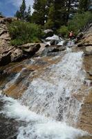 kvinna balanserar vid vattenfall foto