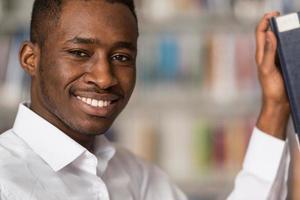 stilig ung högskolestudent i ett bibliotek foto