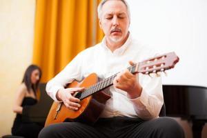 man spelar en akustisk gitarr foto