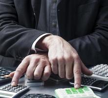 manliga affärshänder som hanterar miniräknare foto