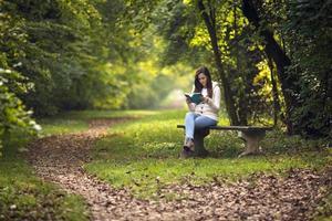 vacker flicka sitter på en parkbänk foto