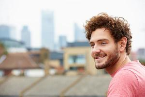 ung man tittar ut över staden från takterrassen foto