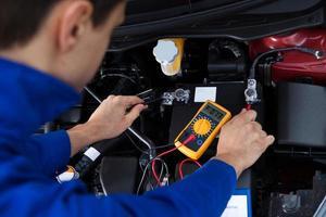 mekaniker som testar bilbatteriet foto