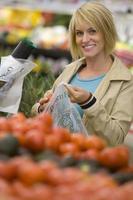 kvinna som väljer tomater i livsmedelsbutik foto