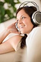 leende kvinna med hörlurar lyssnar på musik i loungen foto