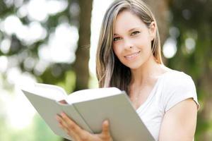 vacker flicka som läser en bok utomhus foto