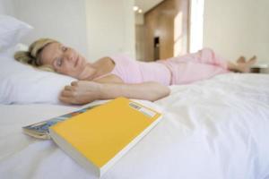 kvinna som ligger på sovande säng, bok i förgrunden foto