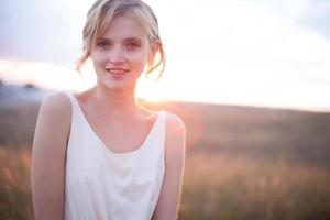 ganska ung kvinna i sommaräng vid gul solnedgång foto