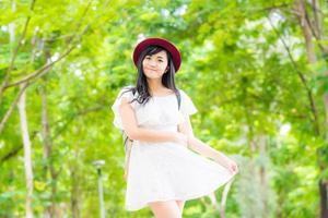stående vacker asiatisk kvinna som går i parken foto