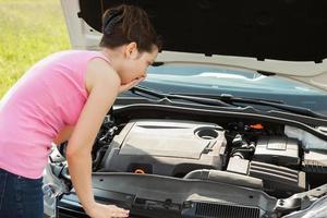 kvinna som tittar under huven bil foto