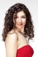 porträtt av ung kvinna med mörkt, lockigt hår foto