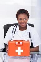 läkare med första hjälpen kit vid skrivbordet på sjukhuset foto