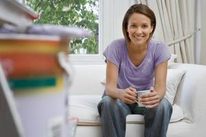 kvinna på soffan med mugg, måla och borste på stegen foto