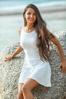 vacker brunettstående på stranden foto