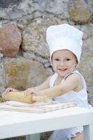 liten pojke med kockhattmatlagning foto