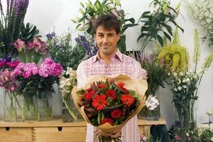 man håller bukett blommor bredvid skärmen i blomsteraffär foto
