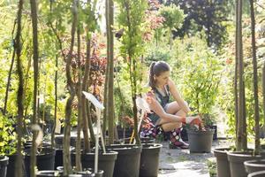 kvinna som planterar kruka i trädgårdscentret foto
