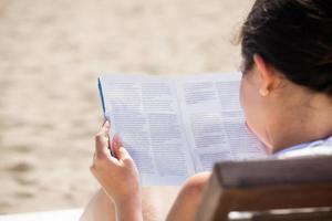 kvinna läser bok på beck stol foto