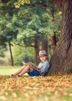 pojke med bok som sitter under stora träd i parken foto