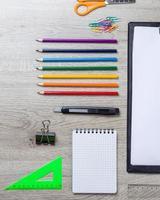 papper, pennor, borste, grönt äpple på träbord