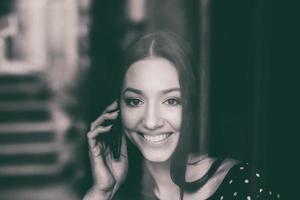 vacker flicka prata i telefon och ler foto