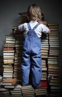 barn räcker efter en bok foto