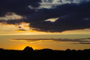 gyllene surrealistisk skymning, dramatisk solnedgång tillbaka upplyst foto
