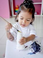liten flicka som har kul att måla på stuckatur foto