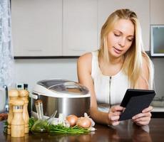 kvinna läser ereader och lagar mat med crockpot foto