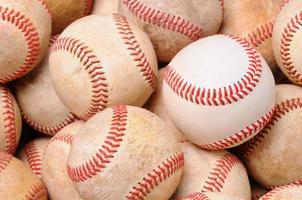 hög med gamla basebollar med en ny boll foto