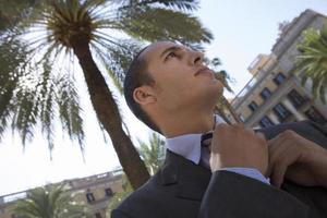 spanien, barcelona, affärsman justerar slips nära palmträdet i pl foto