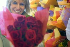 kvinna som håller bukett rosor bredvid butiksdisplay i blomsterhandlare, foto